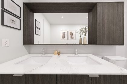 A bathroom, featuring two double sinks and a mirror
