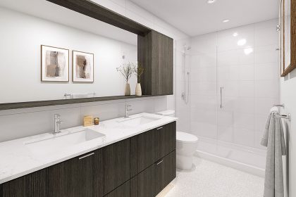 A bathroom from NEST, showing a shower, toilet, sinks, and a large mirror.
