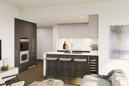 A NEST residence's kitchen, featuring three bar stools. Some of a living area is visible in the foreground.